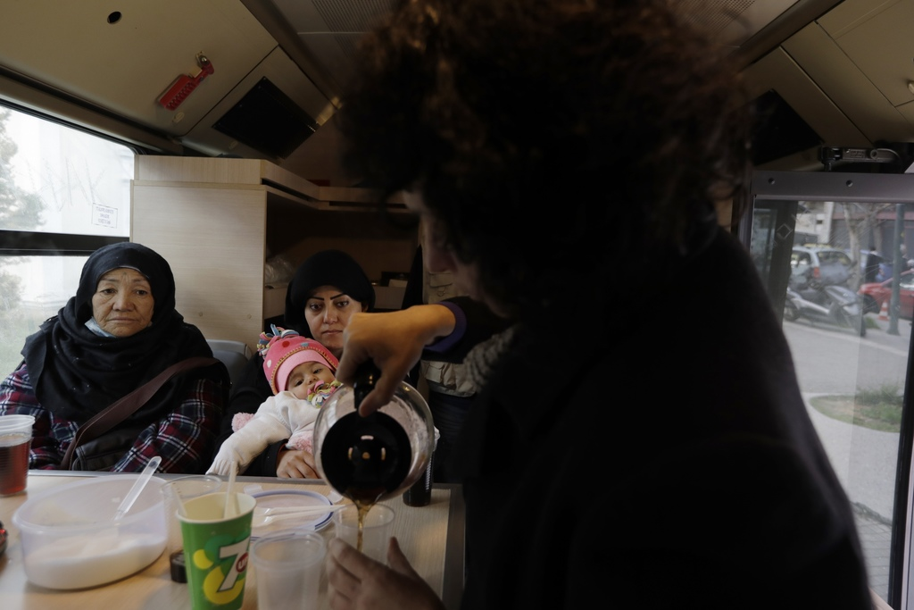 In this photo taken on Wednesday, Dec. 21, 2016, an Afghan refugee family try to warm inside the shower bus, run by the Greek Praksis, ...