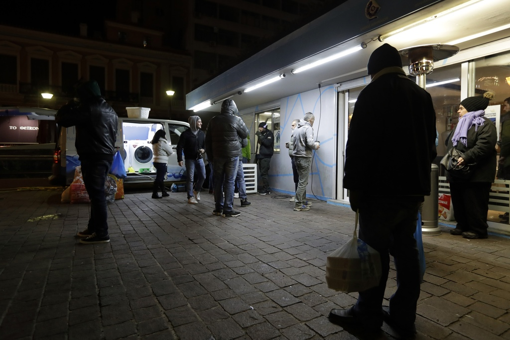In this photo taken on Wednesday, Dec. 21, 2016, homeless persons wait to use the washing machines of Ithaca laundry van in central Ath...