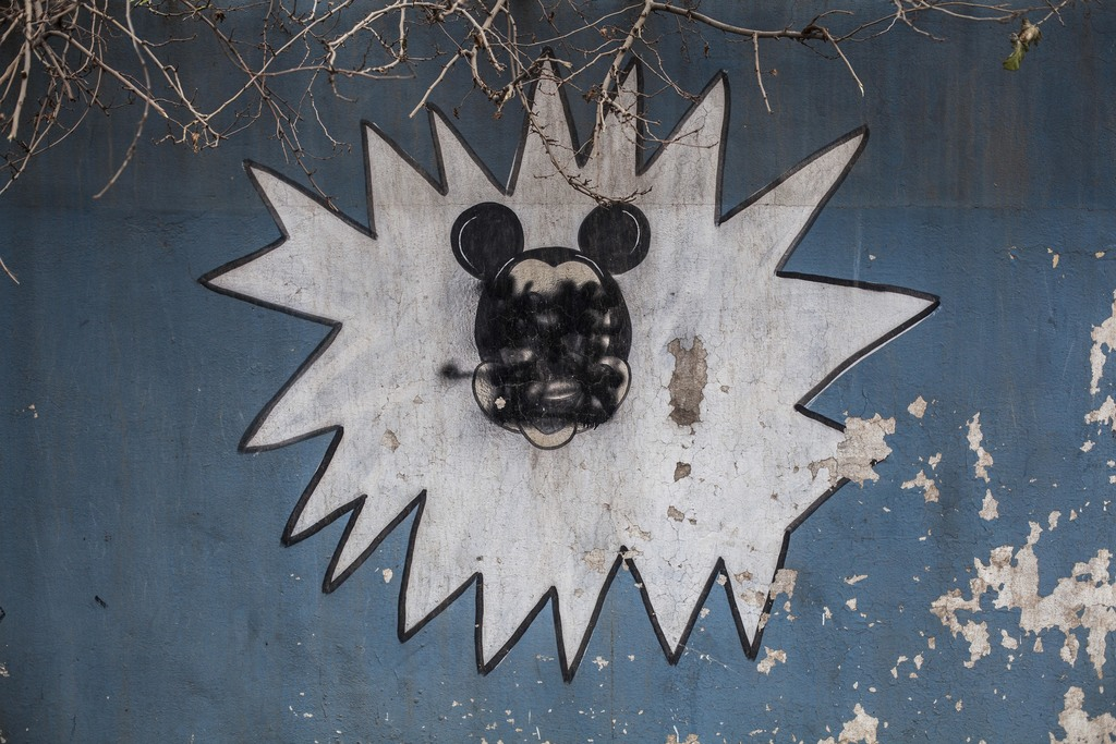 FILE - This Sunday, Dec. 18, 2016 photo shows a drawing of Mickey Mouse with its face painted over by Islamic States militants on the w...