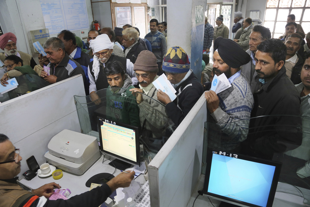 Indians stand in a queue to deposit discontinued notes in a bank in Samba district of Jammu and Kashmir, India, Friday, Dec. 30, 2016. ...