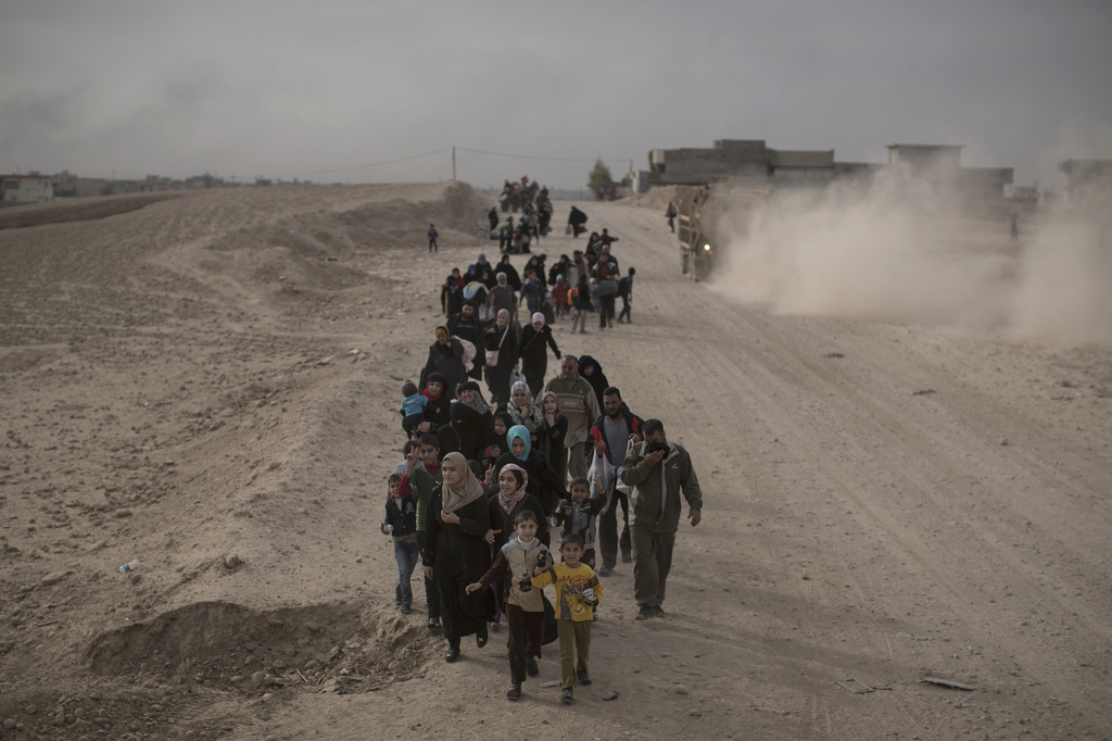FILE - Internally displaced people flee fighting between Iraqi forces and Islamic State militants on a road in eastern Mosul, Iraq, Tue...