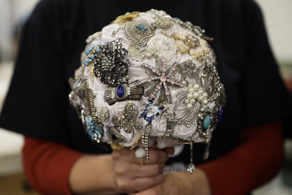 In this Wednesday, Dec. 28, 2016, photo, float decorating volunteer Susan Brown poses with her wedding bouquet in Irwindale, Calif. Bro...