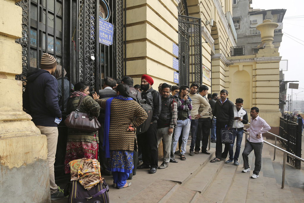 Indians stand in a queue outside a bank in New Delhi, India, Friday, Dec. 30. 2016. India yanked most of its currency bills from circul...