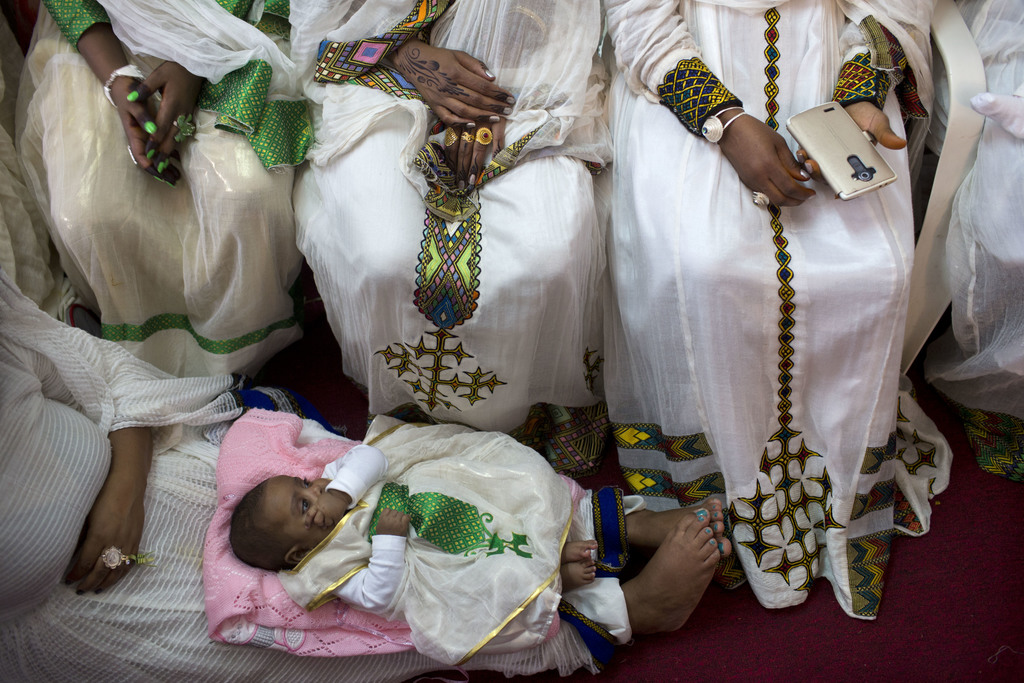 FILE - In this Saturday, April 23, 2016 photo, Eritrean Christian Orthodox migrant women attend a mass at a makeshift church in Tel Avi...