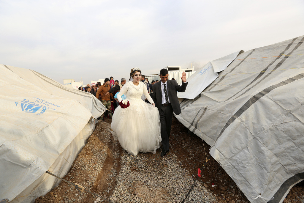 FILE - Iraqi internally displaced groom Jassim Mohammed walks with his bride, Amena Ali, during their wedding ceremony at a camp for in...