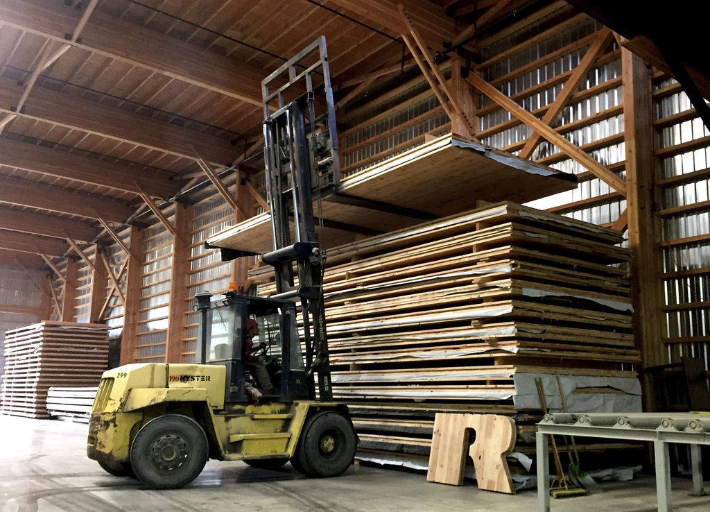 In this Nov. 11, 2016 photo, a forklift driver moves a newly assembled panel of cross-laminated timber, or CLT, to a stack in the produ...