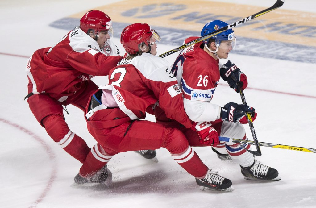 Czech Republic's Adam Musil (26) is held back by Denmark's Niklas Andersen, left, and Anders Koch during the first period of a world ju...