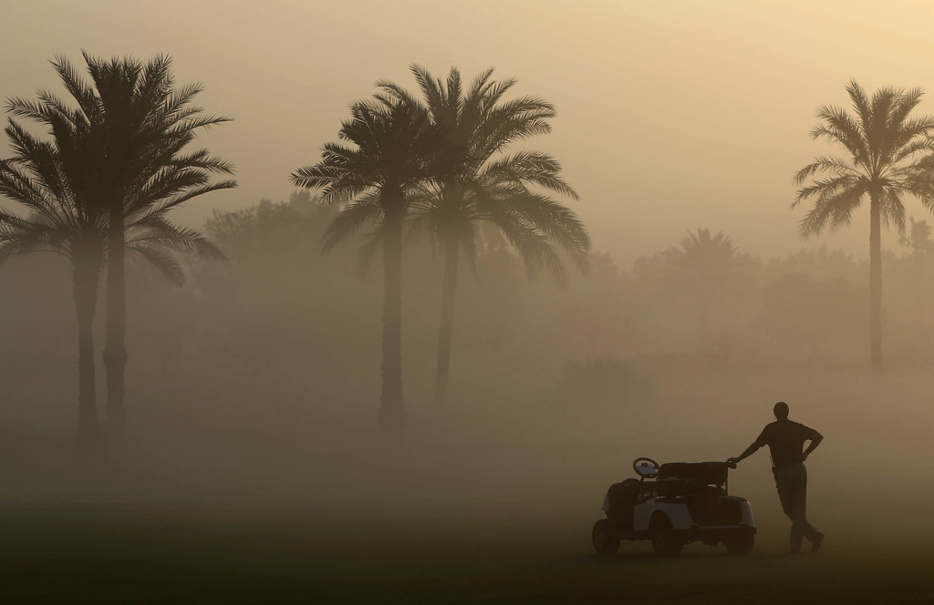 FILE - A martial looks through the early morning fog which delayed the 1st round of Dubai Ladies Masters golf tournament in Dubai, Unit...