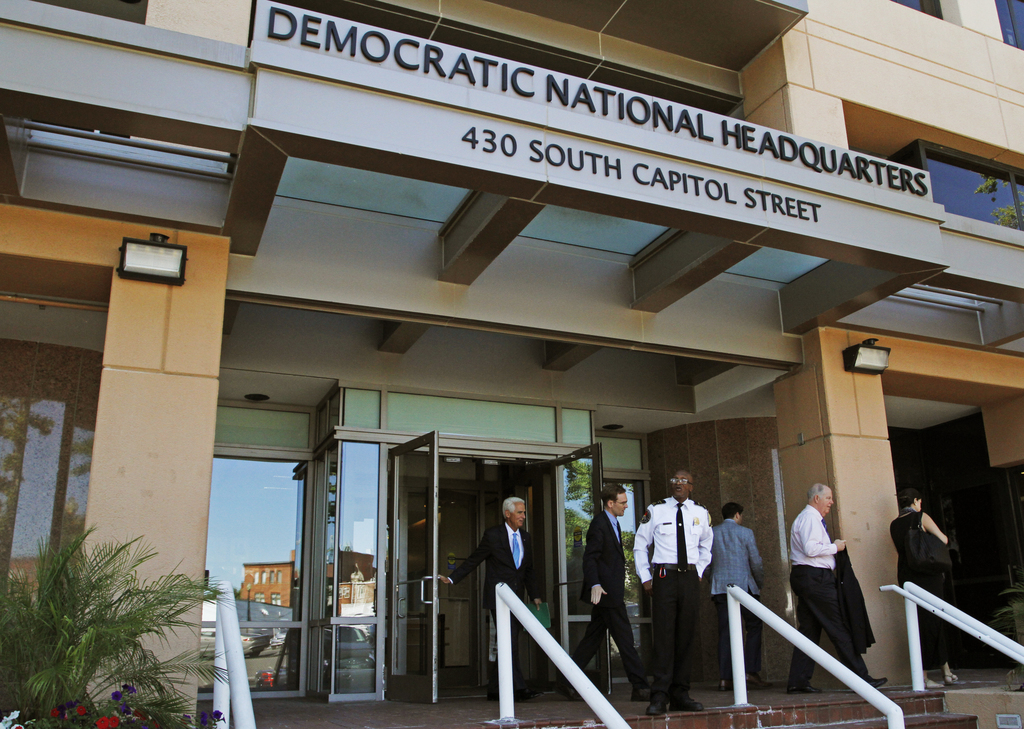 FILE - In this June 14, 2016 file photo, people stand outside the Democratic National Committee (DNC) headquarters in Washington. The U...