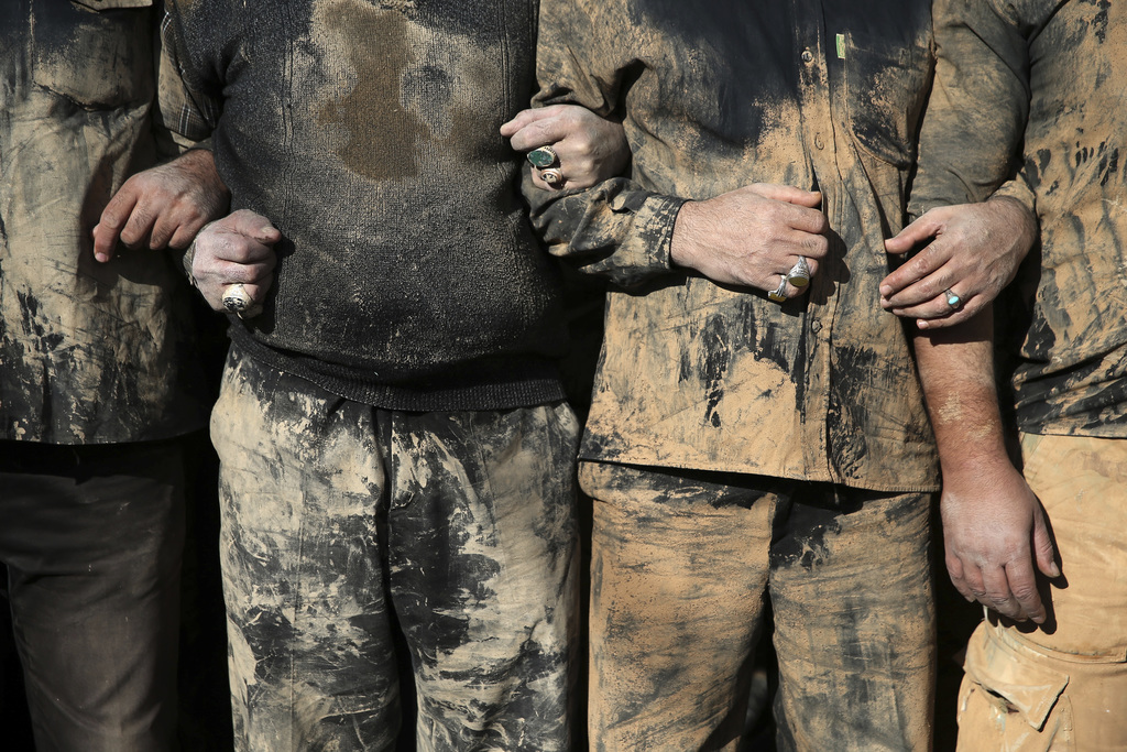 FILE - Iranian Shiite Muslims mourn after covering themselves with mud during Ashoura rituals, in Khorramabad, Iran, Wednesday, Oct.12,...