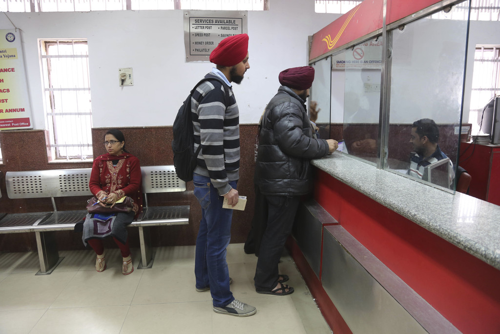 In this Thursday, Dec. 29, 2016 photo, Indians stand to deposit discontinued currency notes at a post office on the outskirts of Jammu,...