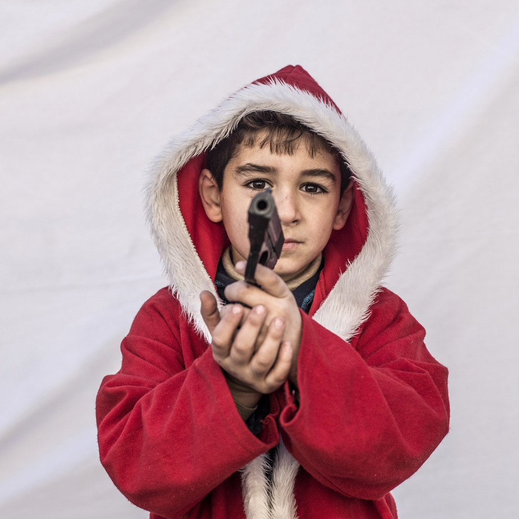 FILE - Kayaks, 7, poses for a picture holding toy gun in a camp where Christians displaced by Islamic State militants are living, in Ir...