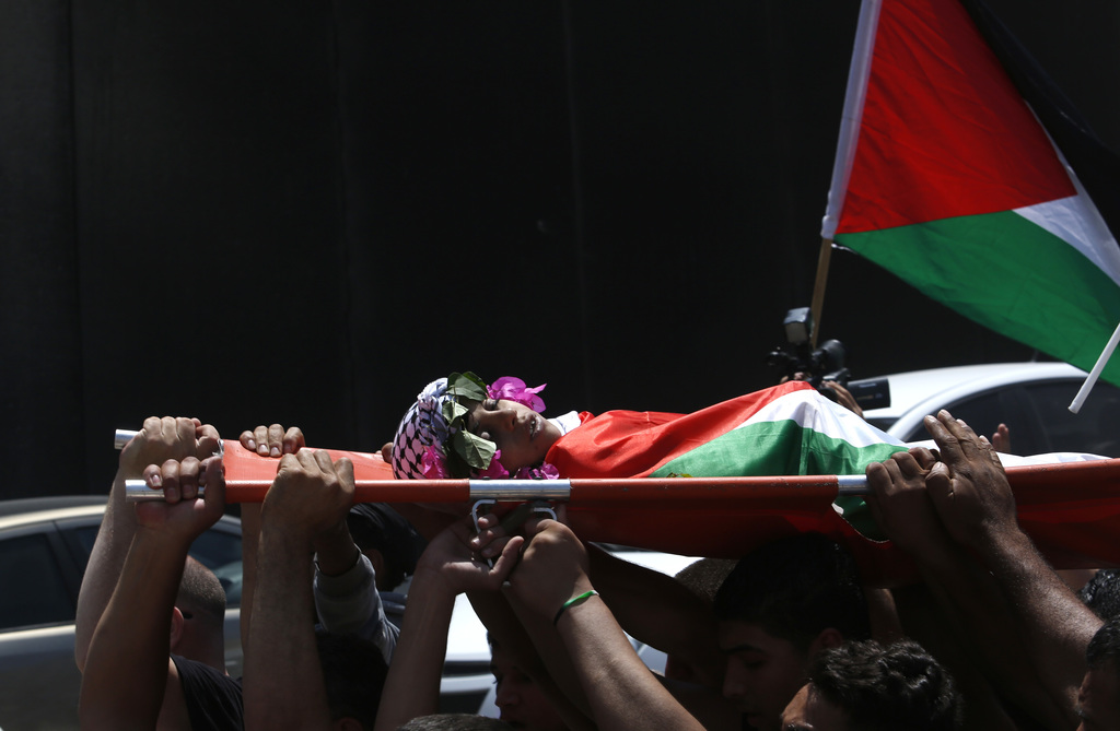 FILE - Mourners walk past the Israeli barrier as they carry the body of Muhey al-Tabakhi, 12, during his funeral in the West Bank town ...