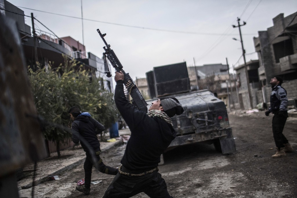 FILE - In this Sunday, Dec. 18, 2016 photo, a member of the Iraqi Special Forces shoots his machine gun against an Islamic State milita...