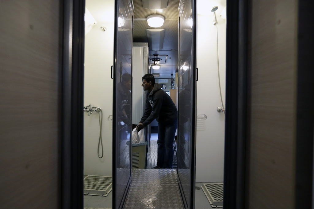 In this photo taken on Monday, Dec. 19, 2016, a homeless person puts a towel into a basket after his shower inside a bus run by the Gre...