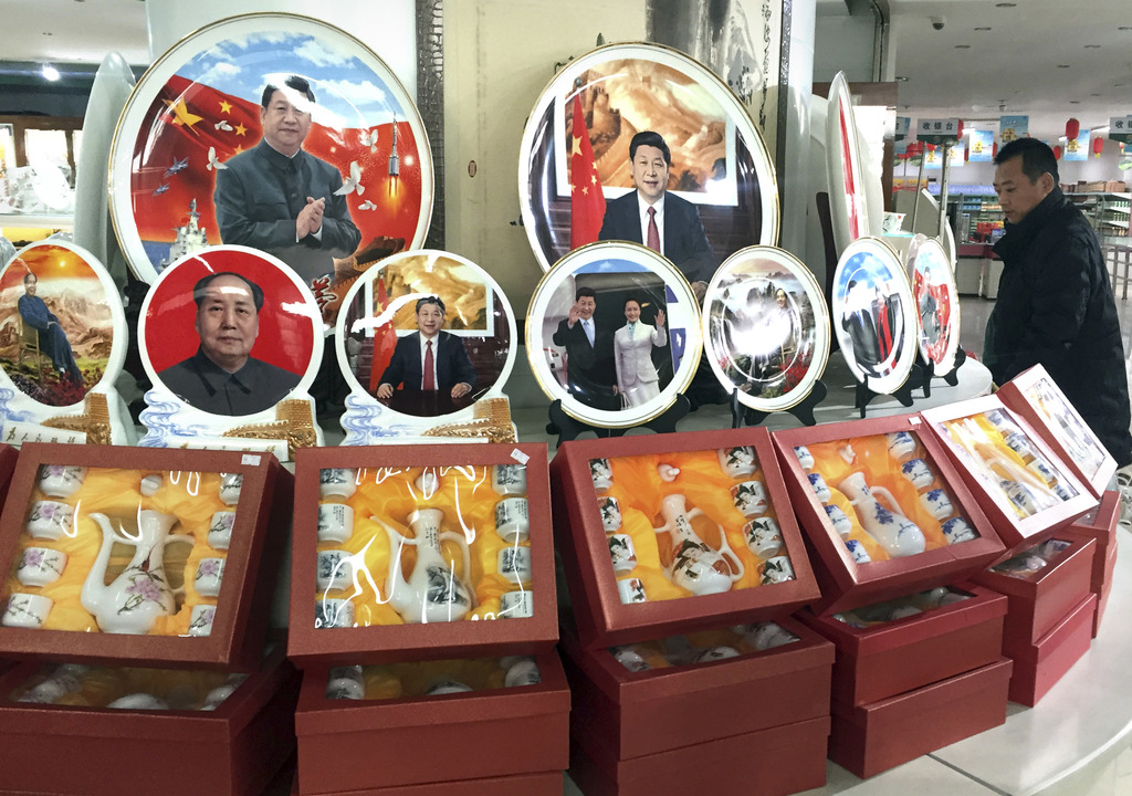 In this photo taken Friday, Dec. 30, 2016, a Chinese man walks past ceramic plates with images of Chinese President Xi Jinping displaye...