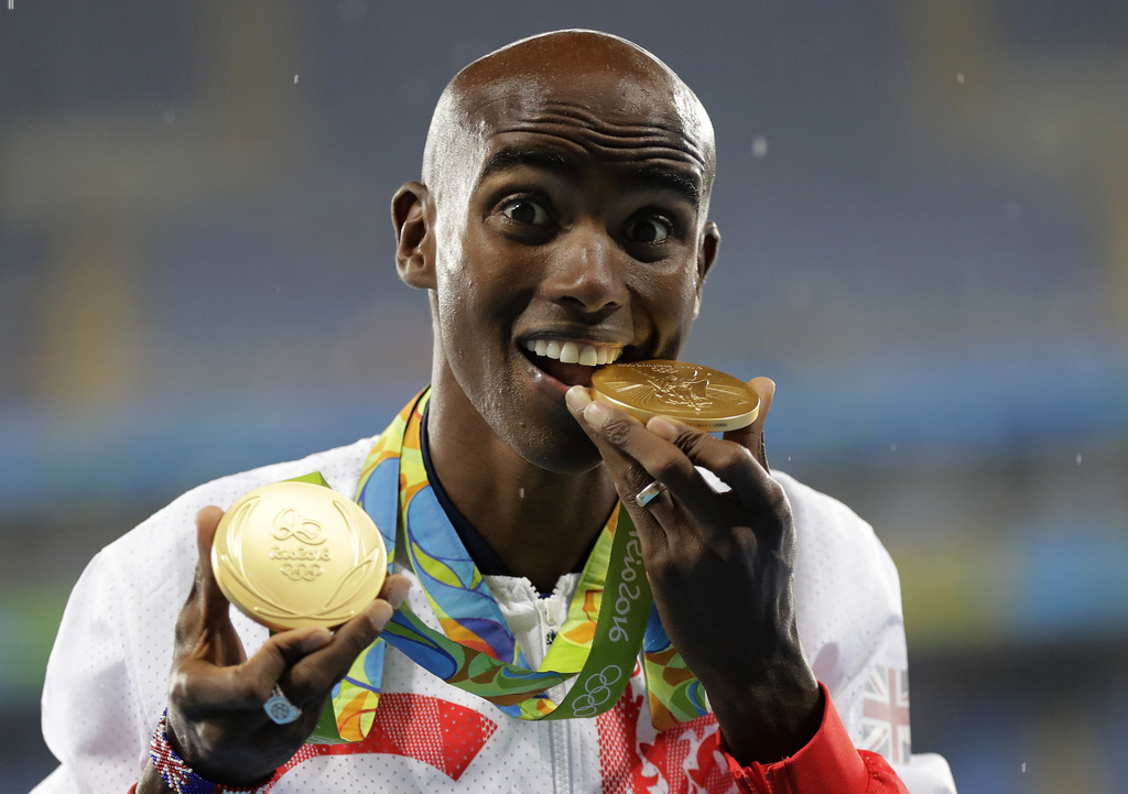 FILE - In this file photo dated Saturday, Aug. 20, 2016, Britain's Mo Farah poses with his gold medals after winning the men's 5000-met...