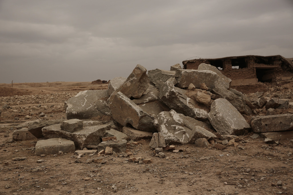 The remains of a large stone figure of a lamassu, an Assyrian winged bull deity, are piled near the gates of the ancient palace where t...