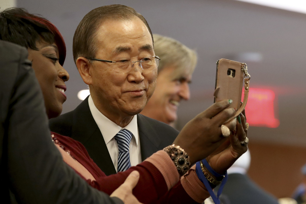 United Nations Secretary-General Ban Ki-moon, poses for a selfie photo with one of his staff members on his last day at the U.N. headqu...