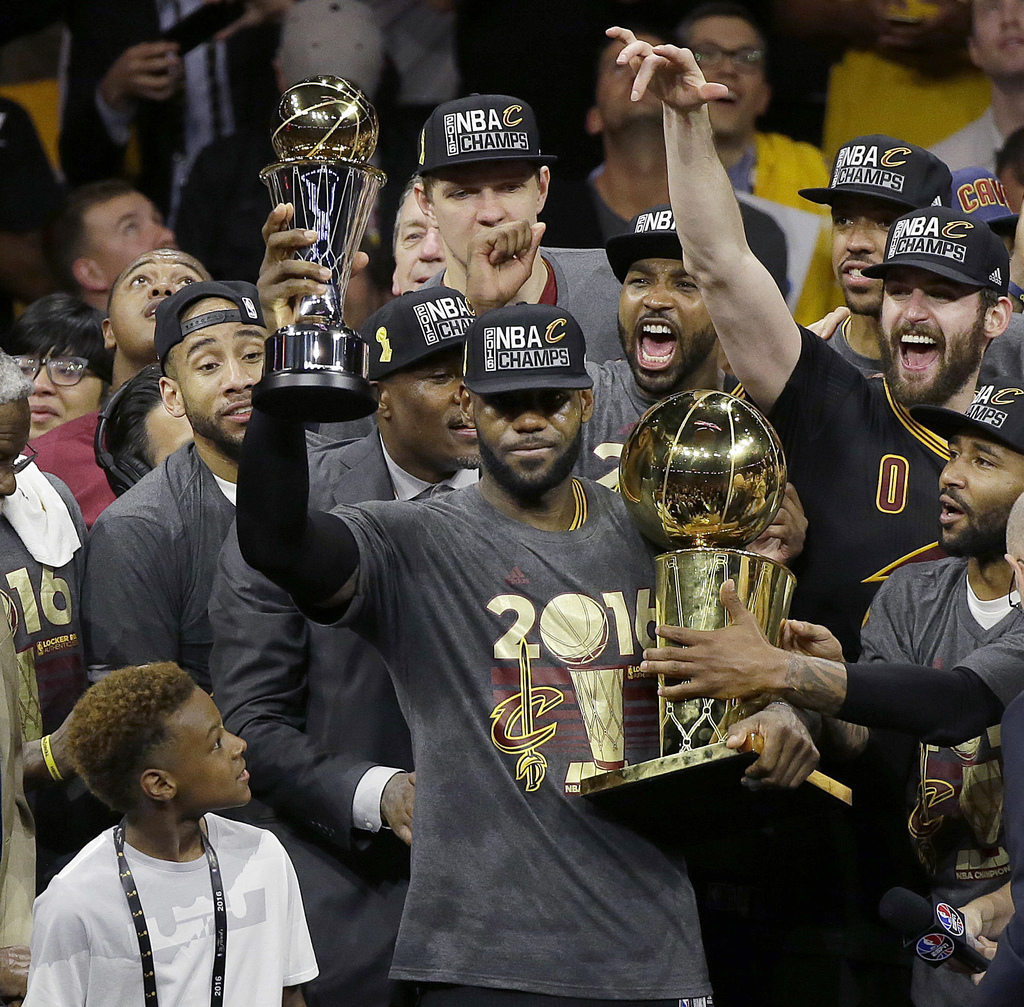 FILE - In this June 19, 2016, file photo, Cleveland Cavaliers forward LeBron James, center, celebrates with teammates after Game 7 of b...