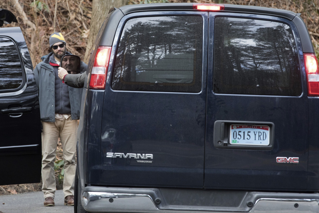 A man driving a van with diplomatic license plates hands his identification to U.S. special agents outside an estate in the village of ...