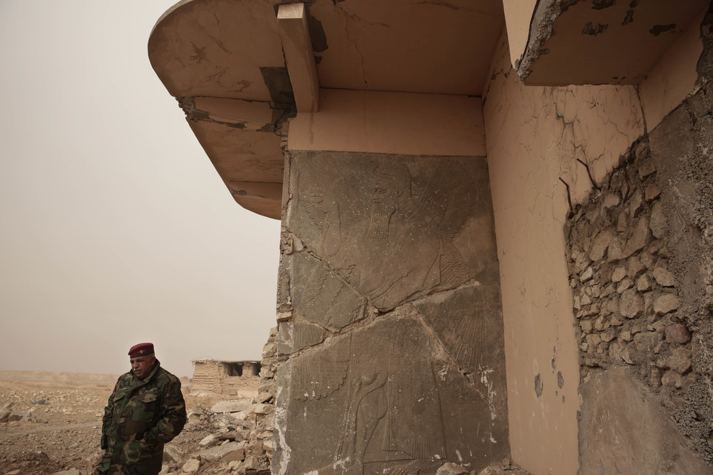 An Iraqi Army general stands near a stone slab depicting a winged genie at the entrance to the Northwest Palace at the ancient site of ...
