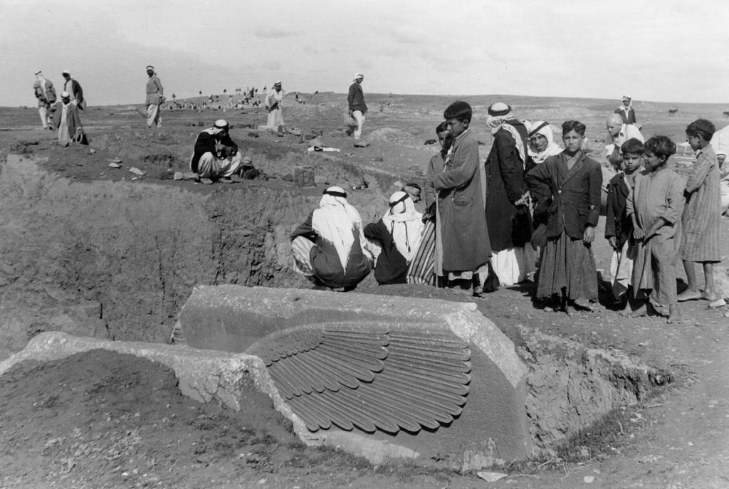 People gather around the partially-unearthed statue of a lamassu, a great winged bull protective deity, in this undated photo taken by ...