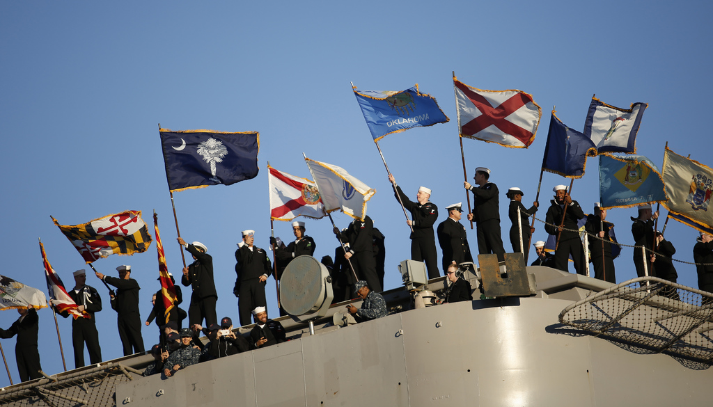 Sailors on the USS Dwight D. Eisenhower wave flags representing different states as the carrier pulled into Naval Station Norfolk, in N...