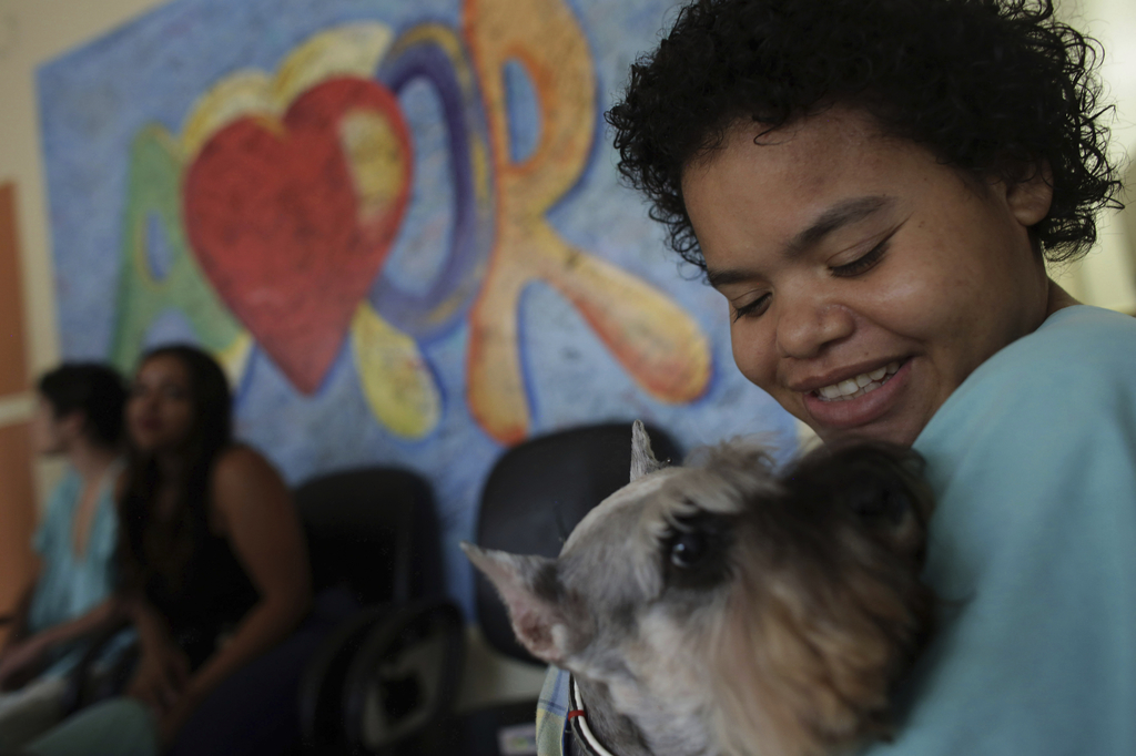 In this Nov. 24, 2016 photo, Jaqueline Castro, a 27-year-old being treated for a degenerative disease, plays with Schnauzer dog named P...