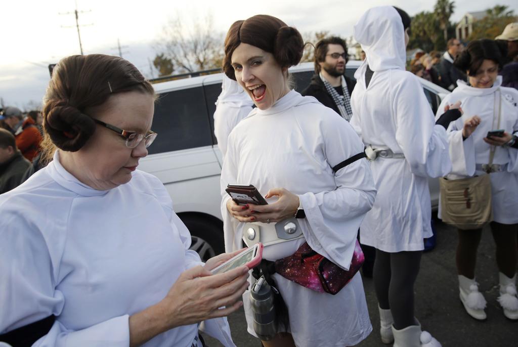 Members of the Krewe of Chewbacchus, a Mardi Gras Krewe, dressed as Princess Leia, use their smart phones at the start of a parade in h...