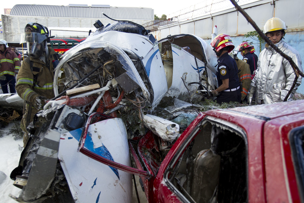 Firefighters and rescue workers surround the wreckage of a small plane that landed on an empty car in a bus parking lot near the Guatem...