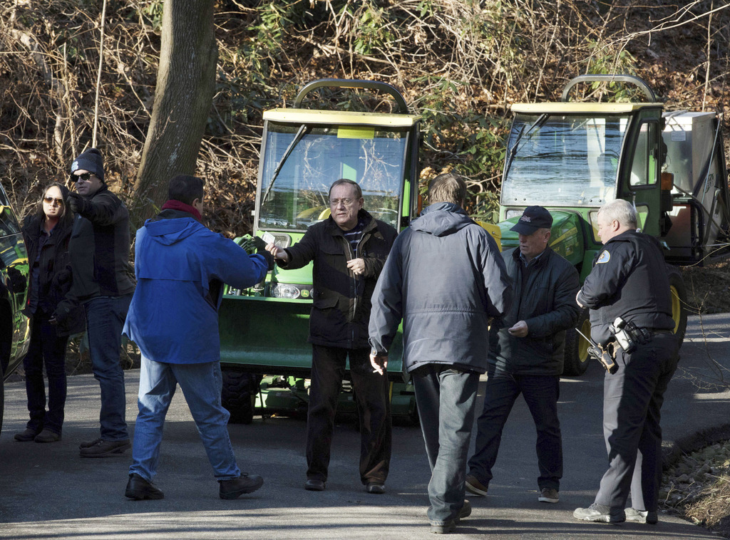 A man, center, hands a card to a federal agent as he and another attempt to drive tractors out of an estate in the village of Upper Bro...