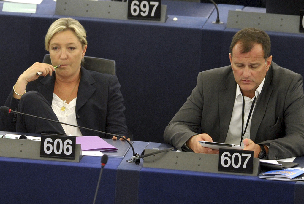 FILE - In this July 15, 2014 file photo, French far right leader Marine Le Pen, left, and party vice-president Louis Aliot listen to de...