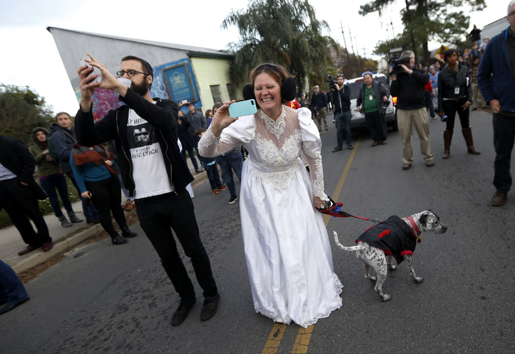 Beckie Wasden, dressed as Princess Leia, takes a photo during a parade in honor of actress Carrie Fisher, who played Princess Leia in t...