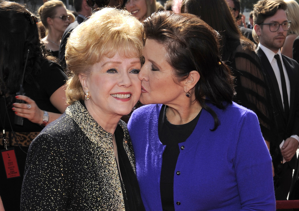 FILE - In this Sept. 10, 2011 file photo, Carrie Fisher kisses her mother, Debbie Reynolds, as they arrive at the Primetime Creative Ar...
