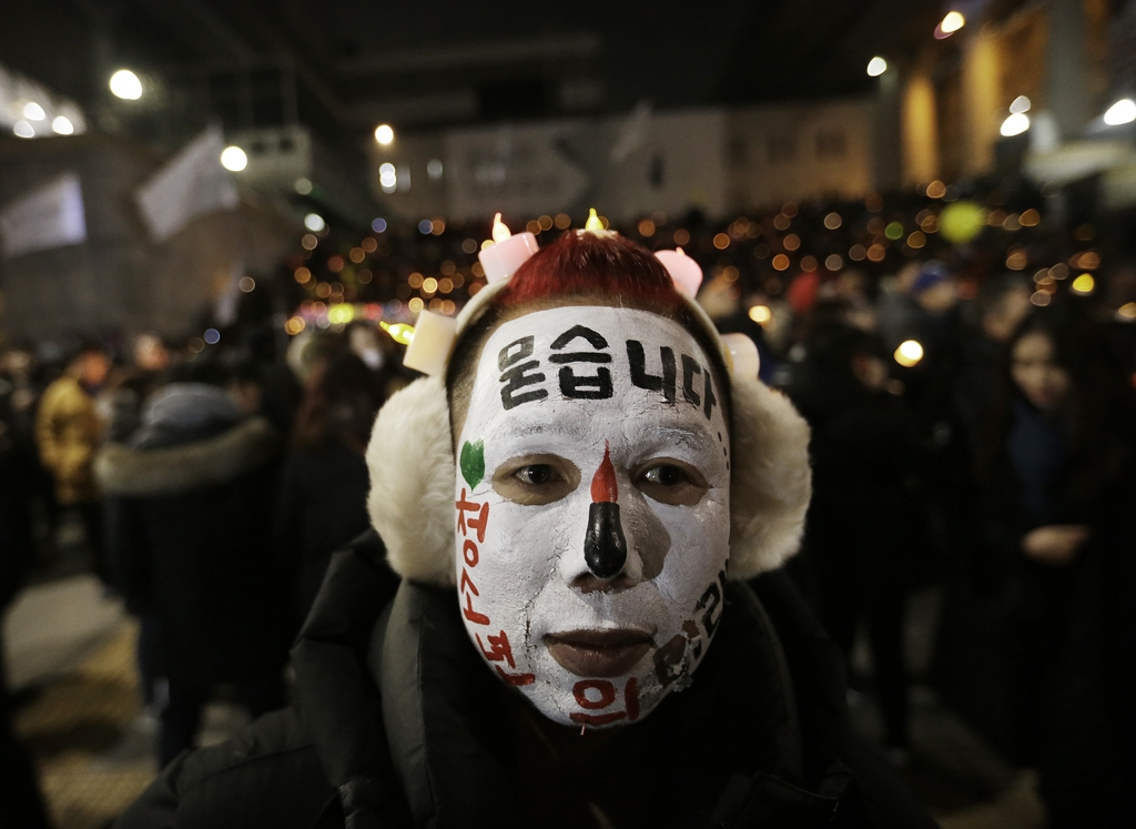 A protester with his face painted attends a candle light vigil calling for impeached President Park Geun-hye to step down in Seoul, Sou...