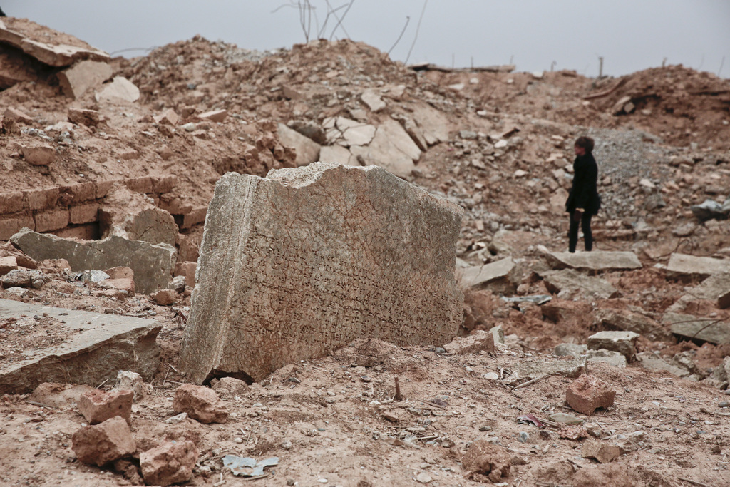 A stone tablet with cuneiform writing is seen in the foreground as UNESCO's Iraq representative Louise Haxthausen documents the damage ...