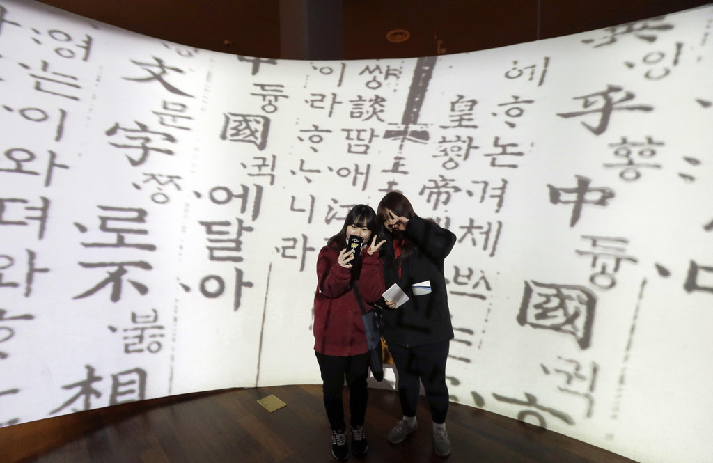 In this Wednesday, Dec. 28 photo, high school students take a selfie in front of a screen showing Korean traditional characters at the ...