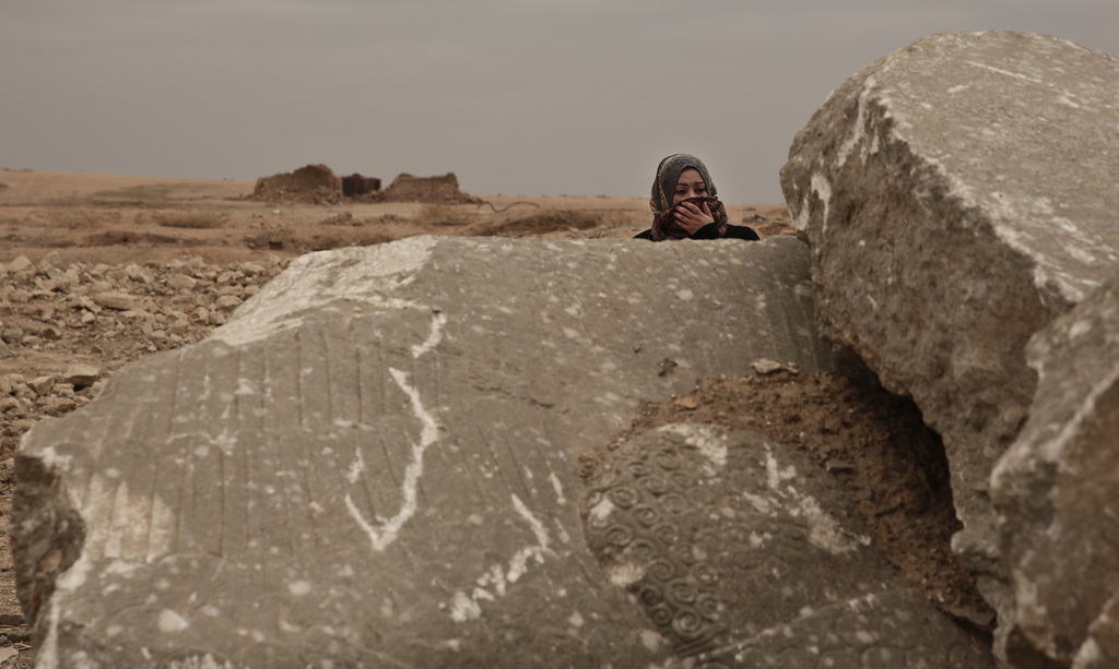 Iraqi archaeologist Layla Salih examines the remains of a statue of a lamassu, a mythical winged bull, destroyed by Islamic State group...