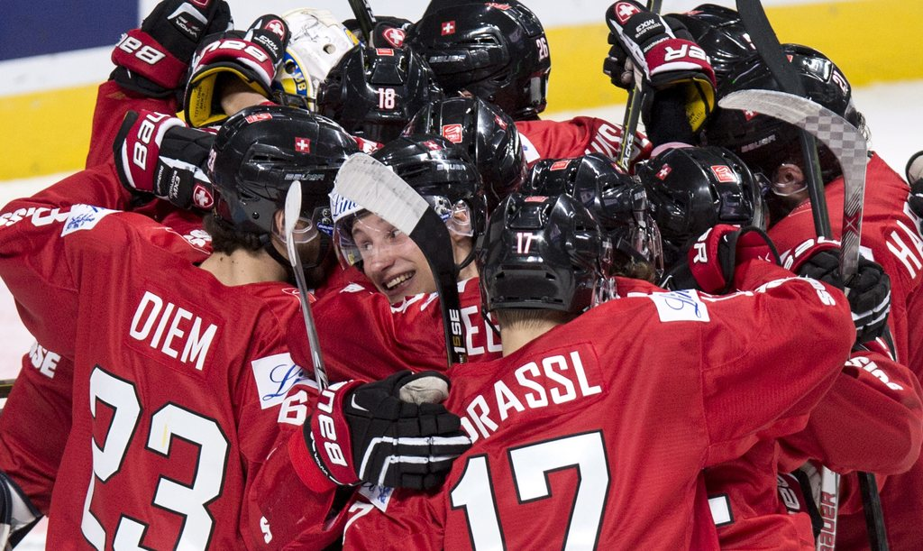 Switzerland's Loic In Albon, center, is surrounded by teammates as they celebrate their 5-4 victory over Denmark in the shootout of a W...