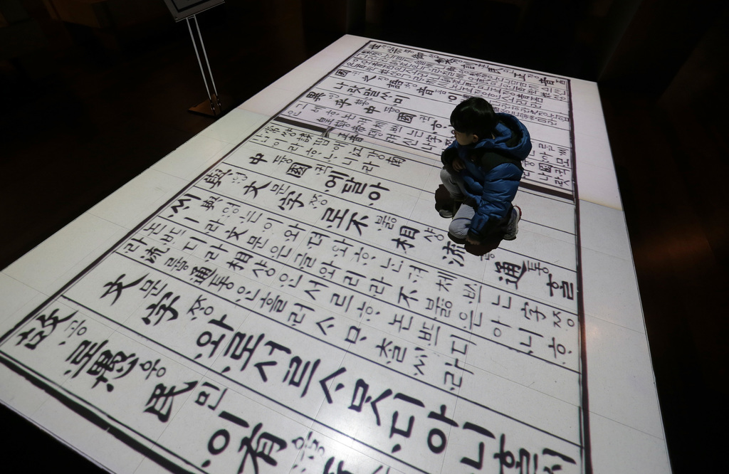 In this Wednesday, Dec. 28 photo, a boy sits on a screen showing Korean traditional characters at the National Hangeul Museum in Seoul,...
