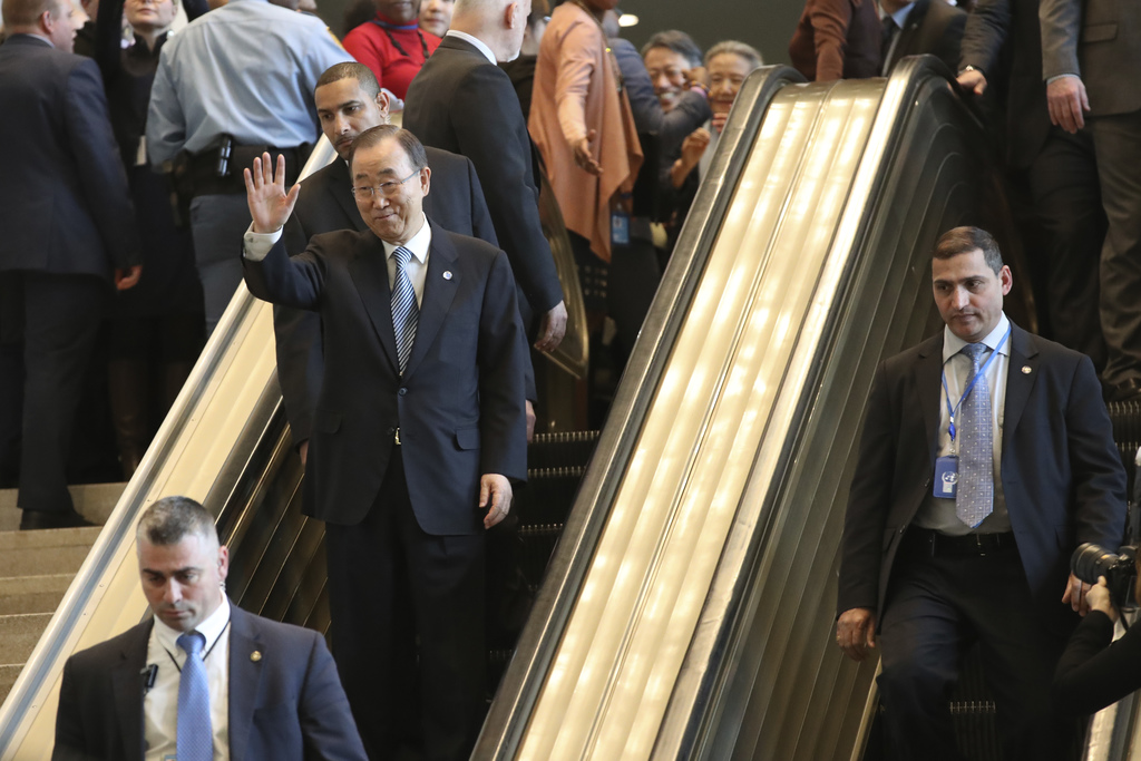 United Nations Secretary-General Ban Ki-moon waves to his staff as he leaves on his last day at the U.N. headquarters, Friday, Dec. 30,...