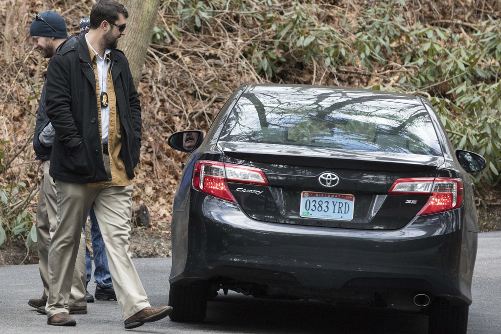 U.S. special agents check a car with diplomatic license plates outside an estate in the village of Upper Brookville in the town of Oyst...