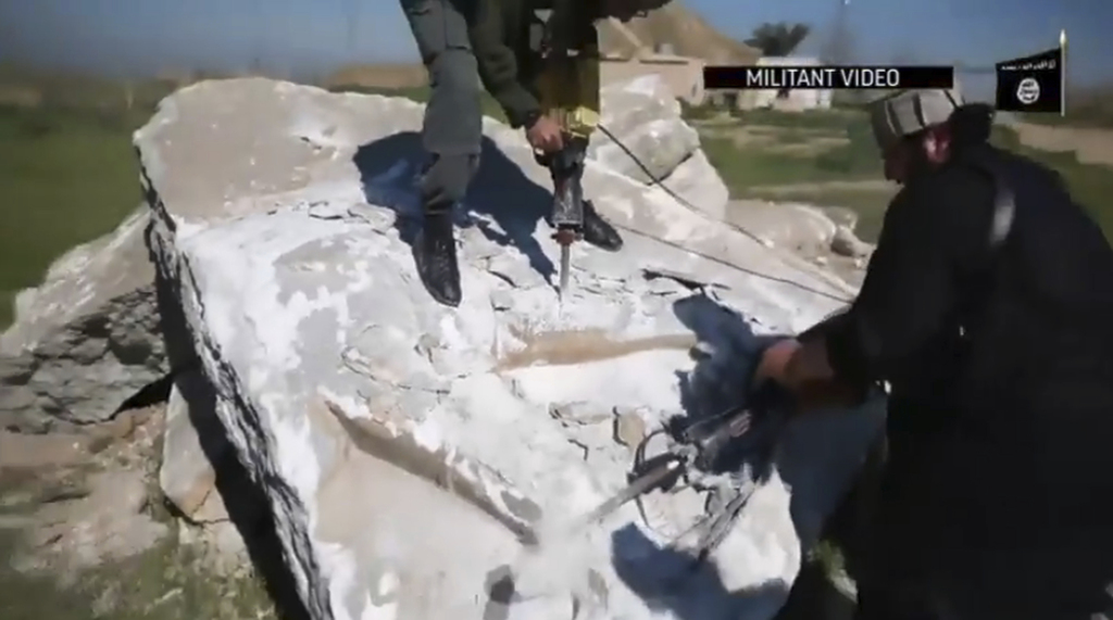 FILE - This image made from video posted online by Islamic State group militants in April 2015 shows militants using heavy tools to des...
