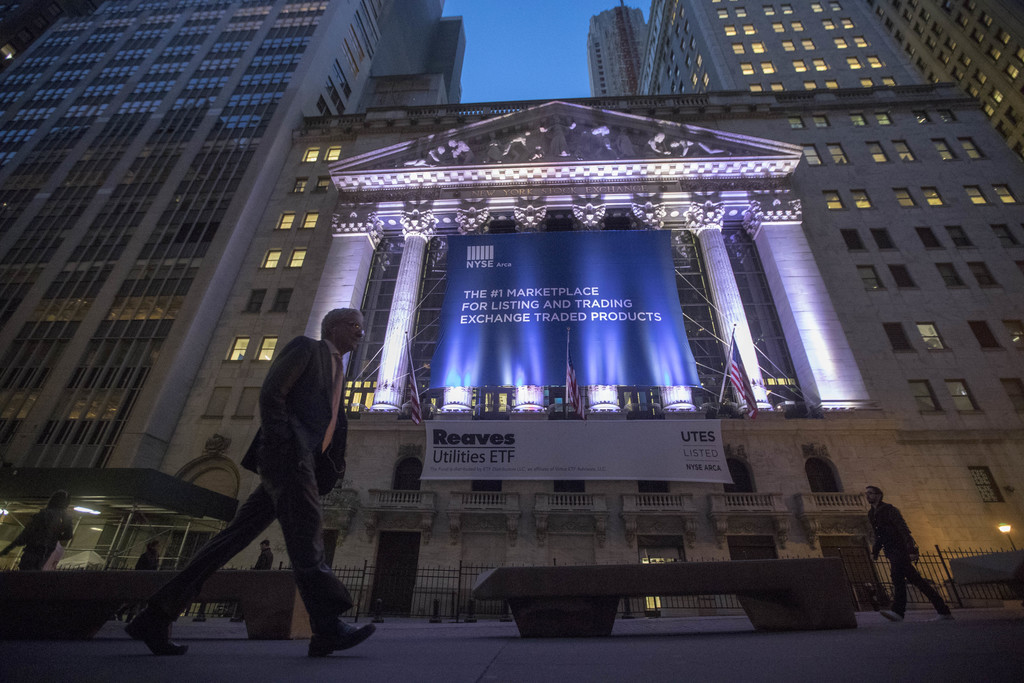 FILE - In this Oct. 25, 2016, photo, a pedestrian passes the New York Stock Exchange, in lower Manhattan. U.S. stocks edged higher Frid...