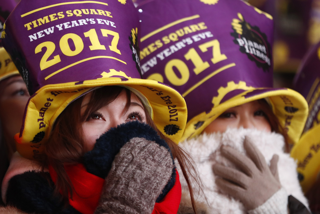Revelers bundle up while gathered at Times Square during a New Year's Eve celebration Saturday, Dec. 31, 2016, in New York. (AP Photo/J...