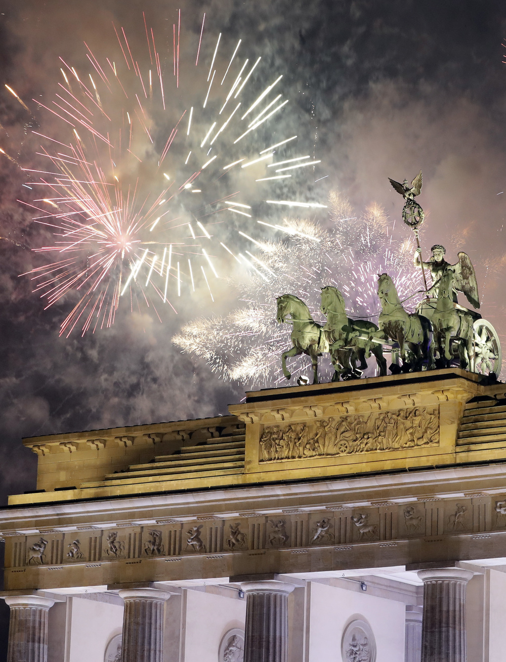 Fireworks light the sky above the Quadriga at the Brandenburg Gate shortly after midnight in Berlin, Germany, Sunday, Jan. 1, 2017. Hun...