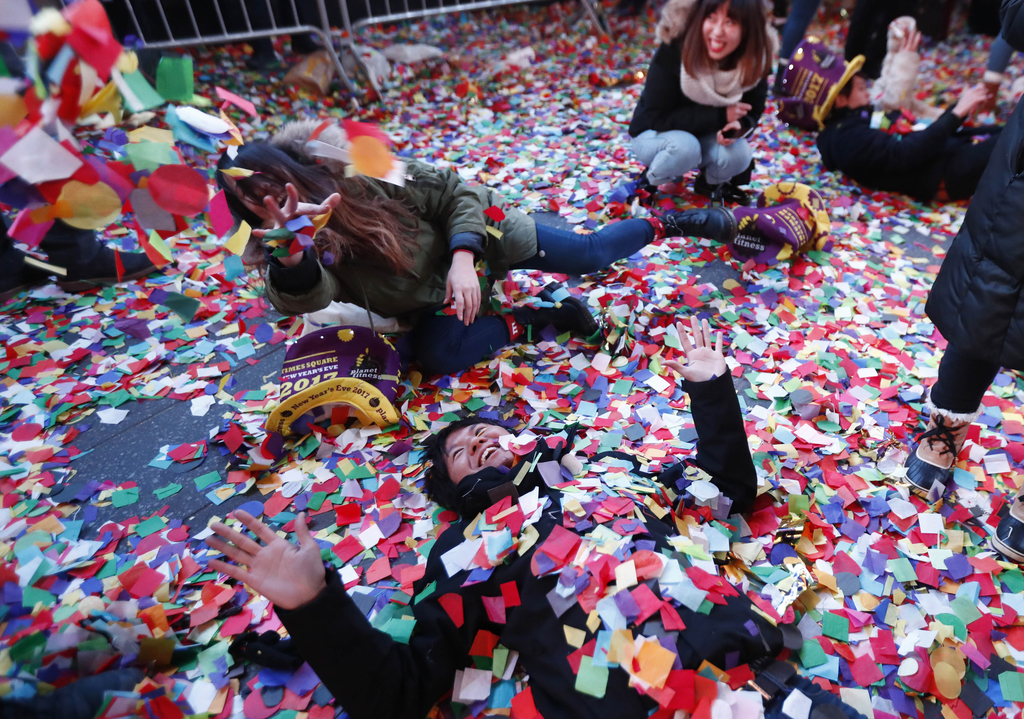 Revelers throw confetti on themselves after after celebrating the new year in Times Square, Sunday, Jan. 1, 2017, in New York. (AP Phot...