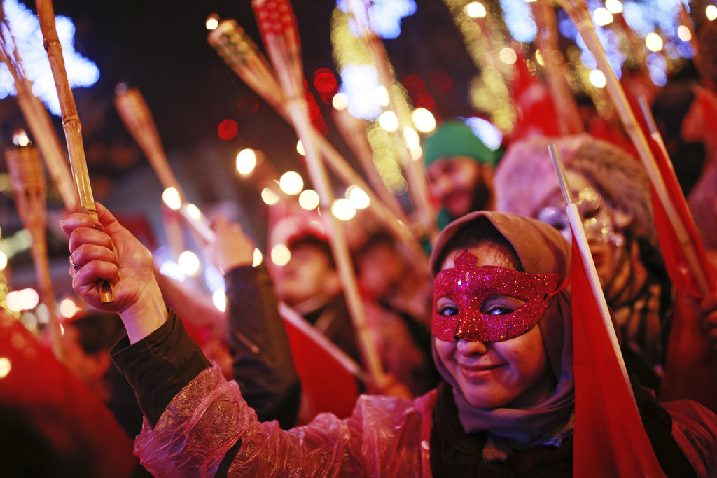 People hold torches during New Year's cerebrations in Istanbul's Ortakoy district by the Bosphorus, during New Year's cerebrations, lat...