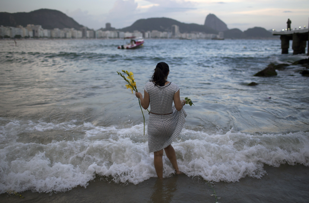 A woman offers flowers to Yemanja, goddess of the sea, for good luck in the coming year during New Year's Eve festivities on Copacabana...
